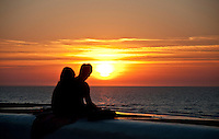 A silhouetted couple watching the sun set in Villers-sur-Mer, Normandy, France.