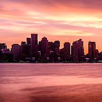 Boston skyline picture with colorful sunset. Scene includes downtown Boston city skyscraper buildings across Boston Harbor.