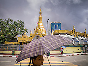 12 JUNE 2013 - YANGON, MYANMAR:  A woman walks past Sule Pagoda in Yangon, Myanmar. Sule Pagoda is one of the city's oldest and most revered Buddhist temples and landmark for central Yangon.        PHOTO BY JACK KURTZ