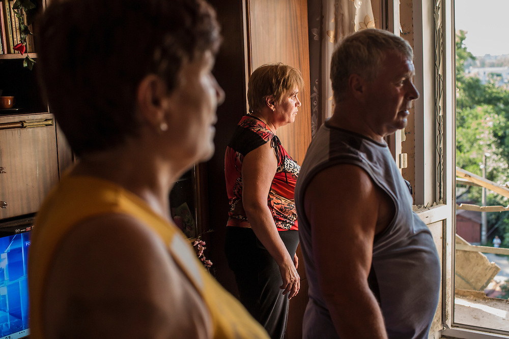 People clean up an apartment which was heavily damaged by a suspected grad rocket strike on Tuesday, July 29, 2014 in Donetsk, Ukraine.