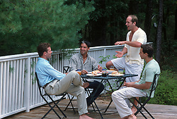 Four men sitting around a table having lunch outdoors on a backyard deck