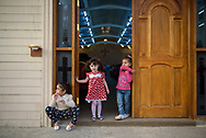 Three girls hang out in the doorway during a service at Mart Shmoni church, a Syriac Catholic church in Ankawa, a suburb of Erbil, Iraq. Most of the parisioners are IDPs, pushed out of their homes in Qaraqosh during the 2014 ISIS advance. (May 2, 2017)