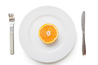 Cross section of an orange in plate with fork and knife over white background