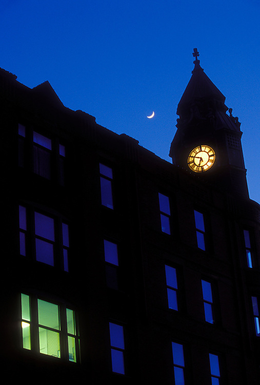 A single office is lit in the historic Savings Bank building in downtown Marquette, Mich. as the building is seen with a crescent moon at dusk.