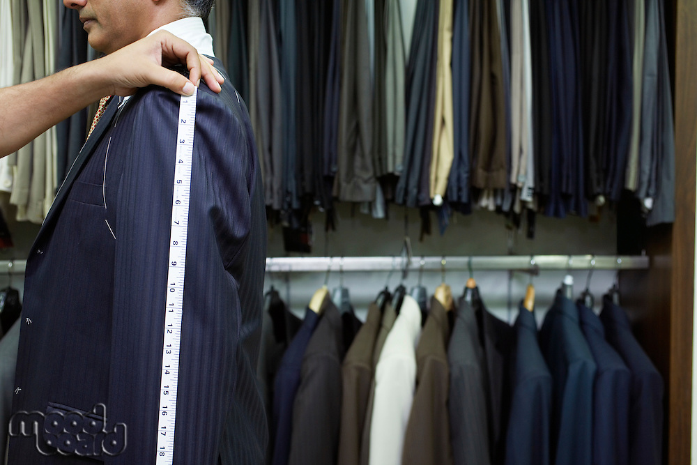 Tailor measuring business man for suit side view