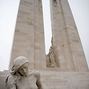 The female mourner sculpture in front of the twin white pylons of the ‪Canadian National Vimy Memorial‬ dedicated to the memory of Canadian Expeditionary Force members killed in World War one. The monument is situated at a 100 hectare preserved battlefield with wartime tunnels, trenches, craters and unexploded munitions. The memorial designed by Walter Seymour Allward opened in 1936.