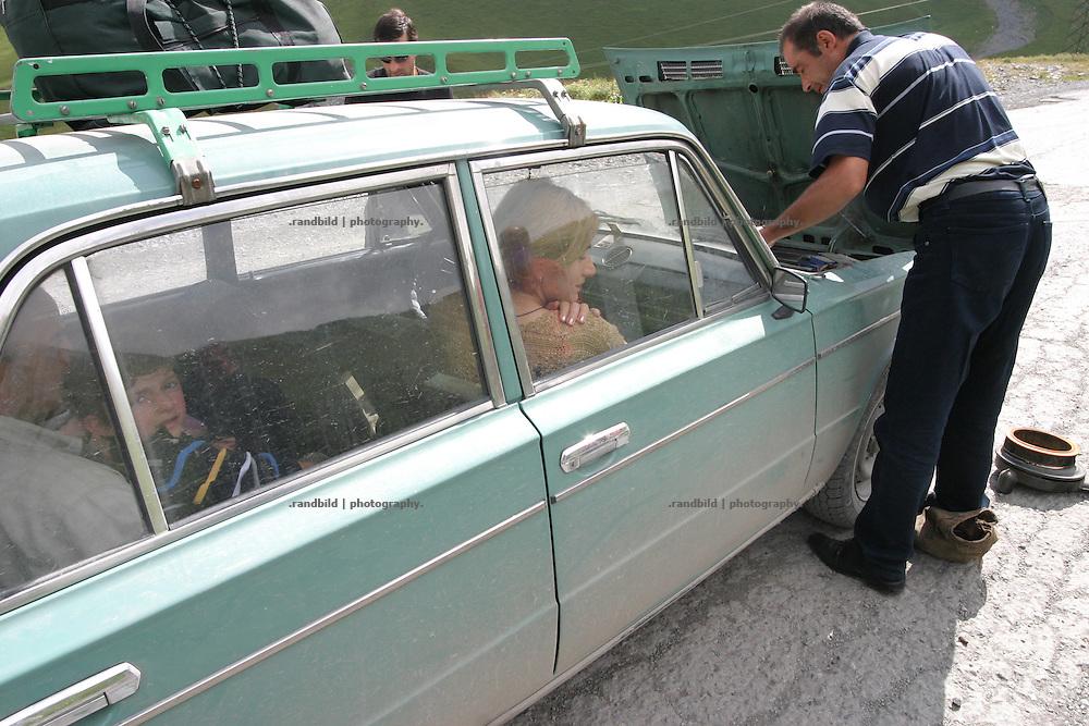 Ein Schiguli ist ist am Kreuzpass (2400 m.) auf der Georgischen Heerstrasse liegen geblieben. Nicht ungewoehnliches, Georgier wissen sich zu helfen, um ihre alten und anfaelligen Autos wieder flott zu machen. ..A car breakdown on the cross pass (2.400m) on the Georgian Military Highway.