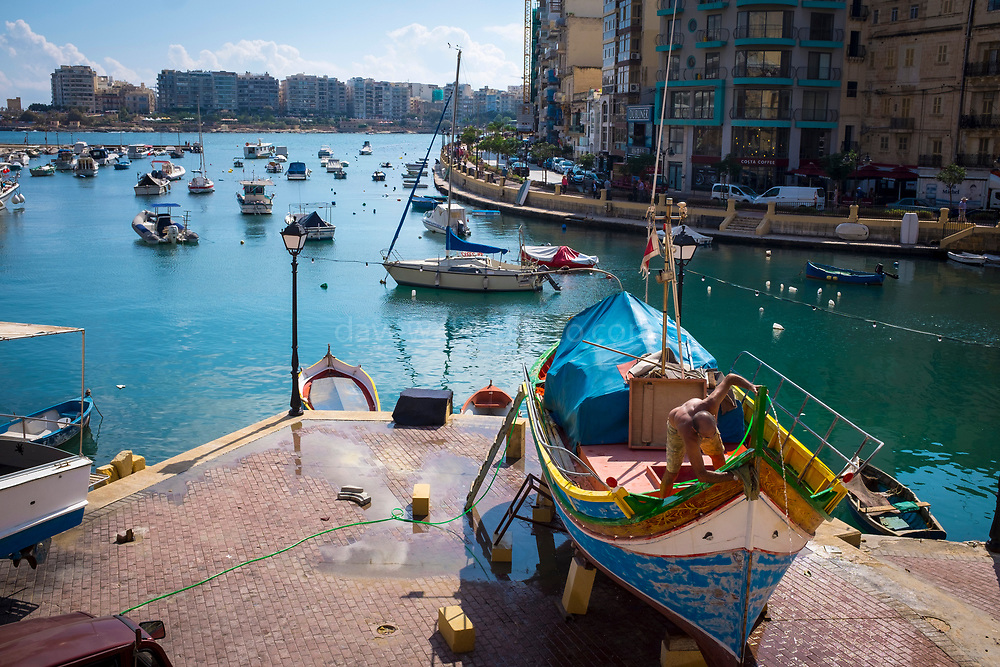Fisherman work on his boat in Spinola Bay, in Saint Julians, Malta