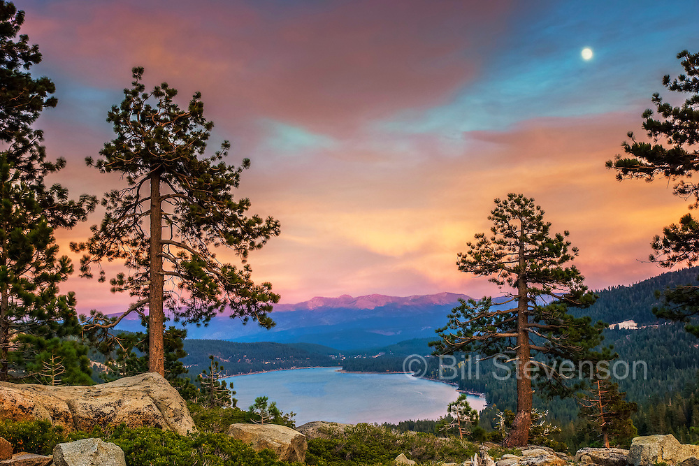 The full moon rising over Donner Lake. Taken at sunset the clouds are golden and the Carson Range is illuminated