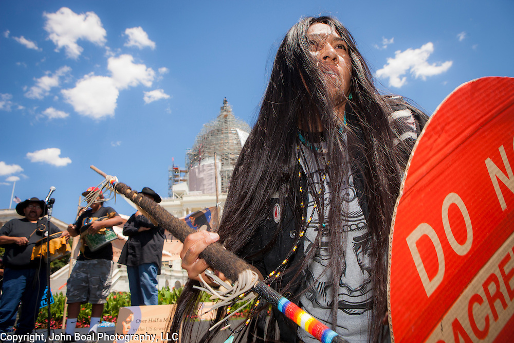 "Carrie Sage Curley, San Carlos Apache, dances to music played by fellow members of the San Carlos Apache Tribe as a demonstration was held in front of the United States Capitol to protest the transfer of Apache land to a private Australian-British mining corporation.  In December 2014, a rider to the National Defense Authorization Act handed over Oak Flat to a foreign-owned company looking to mine copper.  The Apache are currently ""occupying"" Oak Flat, and travelled to D.C. to protest the action.  In response, Rep. Raul Grijalva (D-AZ-3), proposed the Save Oak Flat Act (H.R. 2811) in June, 2015 to repeal the land exchange. John Boal Photography"