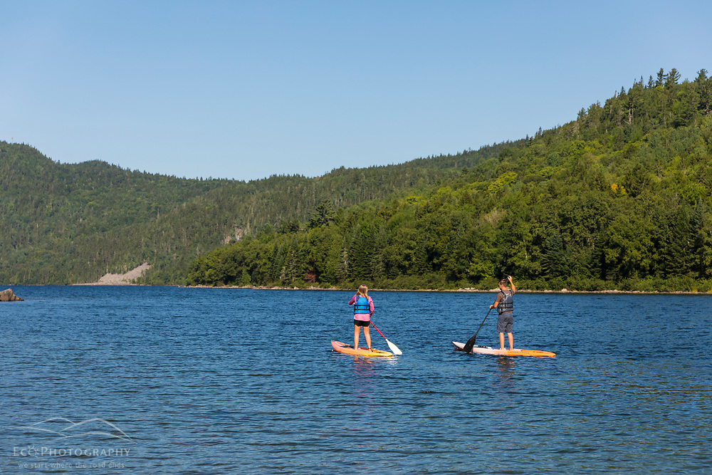 Teenagers paddle stand up paddle boards on Deboullie Pond in Aroostook County, Maine. Deboullie Public Reserve Land.
