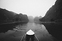 A woman rows a boat down river in northern Vietnam.