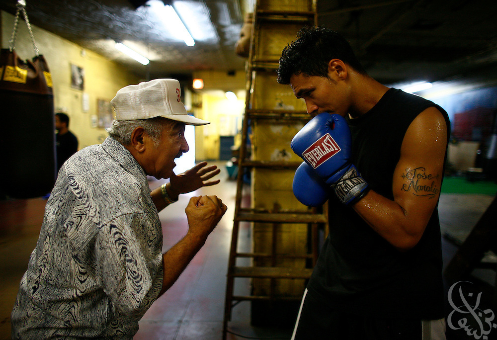 Fort Apache Boxing Club - South Bronx/ NYC  Afternoon, July 20,2006. Trainer Carlos Lope works with a young fighter.  (Photo by Scott Nelson/World Picture Network).