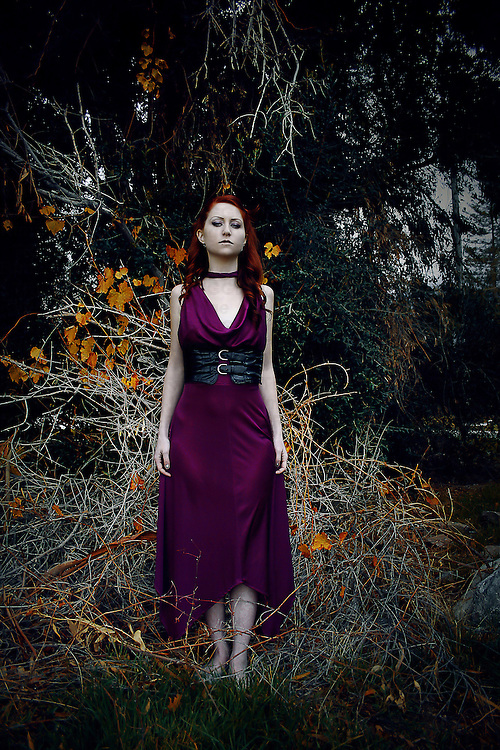 A young woman standing outdoors in woods wearing a purple dress in ivy with golden leaves.