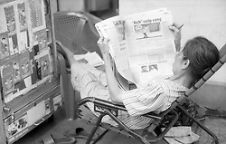 A cigarette vendor takes a break and reads a newspaper in Ho Chi Minh city, Vietnam, Asia.