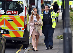 An injured woman is assisted by a police officer close to Parsons Green station in west London after an explosion on a packed London Underground train.