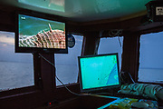 "A World War Two mine caught in fishing nets appears on a television mounted above marine navigation equipment,  installed in the cabin of a fishing boat. Hythe Bay, the English Channel, UK.<br /> Luke skippers his boat alone, to keep him company during the trip he has installed a TV. The journey begins with the opening scene of a Bond film where a Trawler boat nets a mine. ""I've caught a few of those in my time"" say Luke as he navigates around mines, shipwrecks and WWII planes.  Luke is a Folkestone based fisherman out trawling for a 12 hour night shift on a fishing trip in his boat Valentine (FE20), Hythe Bay, the English Channel, UK. (photo by Andrew Aitchison / In pictures via Getty Images)"