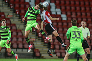 Forest Green Rovers Christian Doidge(9) and Cheltenham Town's Kyle Storer(4) jump for the ball during the EFL Trophy match between Cheltenham Town and Forest Green Rovers at Whaddon Road, Cheltenham, England on 3 October 2017. Photo by Shane Healey.