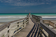 A young woman looks out at the  clear turquoise water from a  walkway to the beach at Folly Beach, SC.