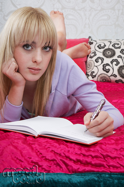 Portrait of teenager (16-17) lying on bed writing diary