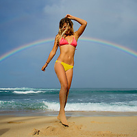 Woman playing on the beach beneath a rainbow on the North Shore of Oahu.