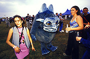 Two clubbers at Creamfields standing by a blue monster, UK 2000's