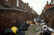 Bin-bags and refuse in back-to-back housing alleyway during the Merseyside dustmens' strike of 199