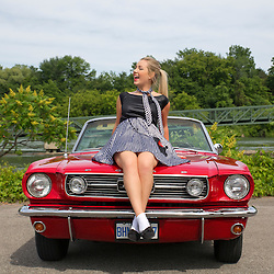A young blonde in a poodle skirt sitting on the hood of a 1966 Ford Mustang 289 convertible.