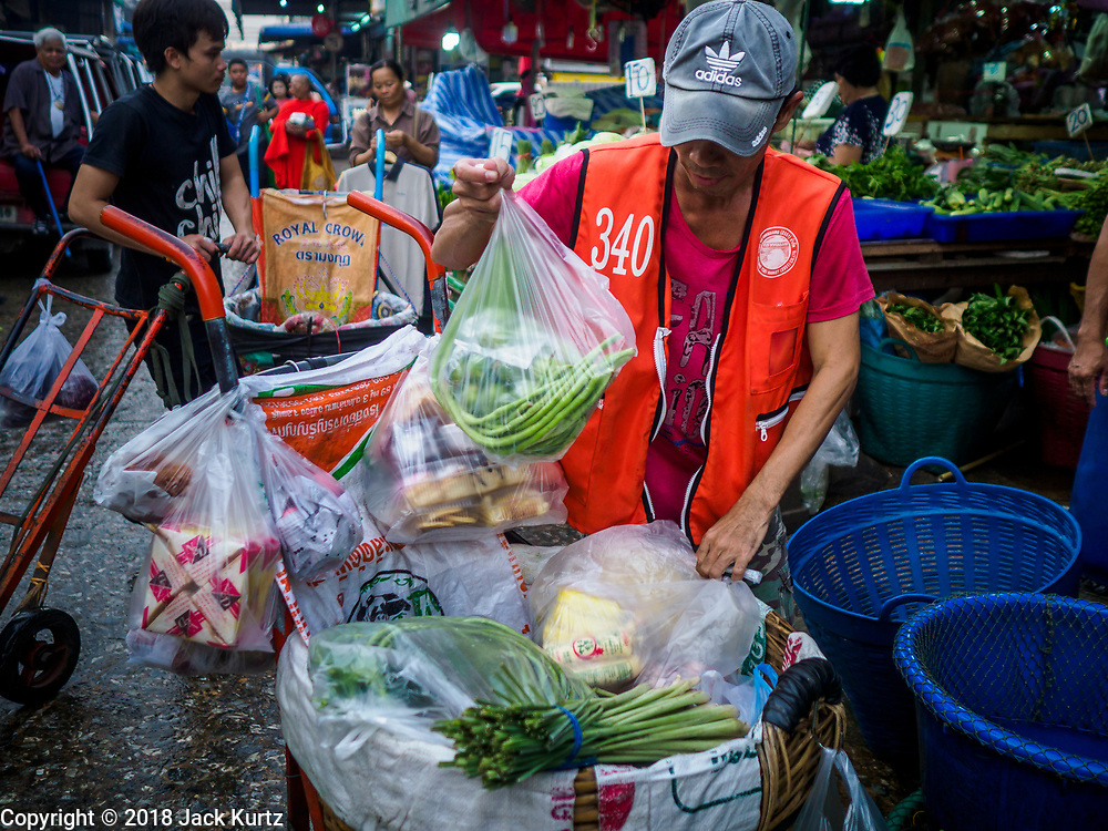 "04 DECEMBER 2018 - BANGKOK, THAILAND:  A porter packs up a customer's produce purchase, packaged in single use plastic bags. The issue of plastic waste became a public one in early June when a whale in Thai waters died after ingesting 18 pounds of plastic. In a recent report, Ocean Conservancy claimed that Thailand, China, Indonesia, the Philippines, and Vietnam were responsible for as much as 60 percent of the plastic waste in the world's oceans. Khlong Toey (also called Khlong Toei) Market is one of the largest ""wet markets"" in Thailand. December 4 was supposed to be a plastic free day in Bangkok but many market venders continued to use plastic.    PHOTO BY JACK KURTZ"