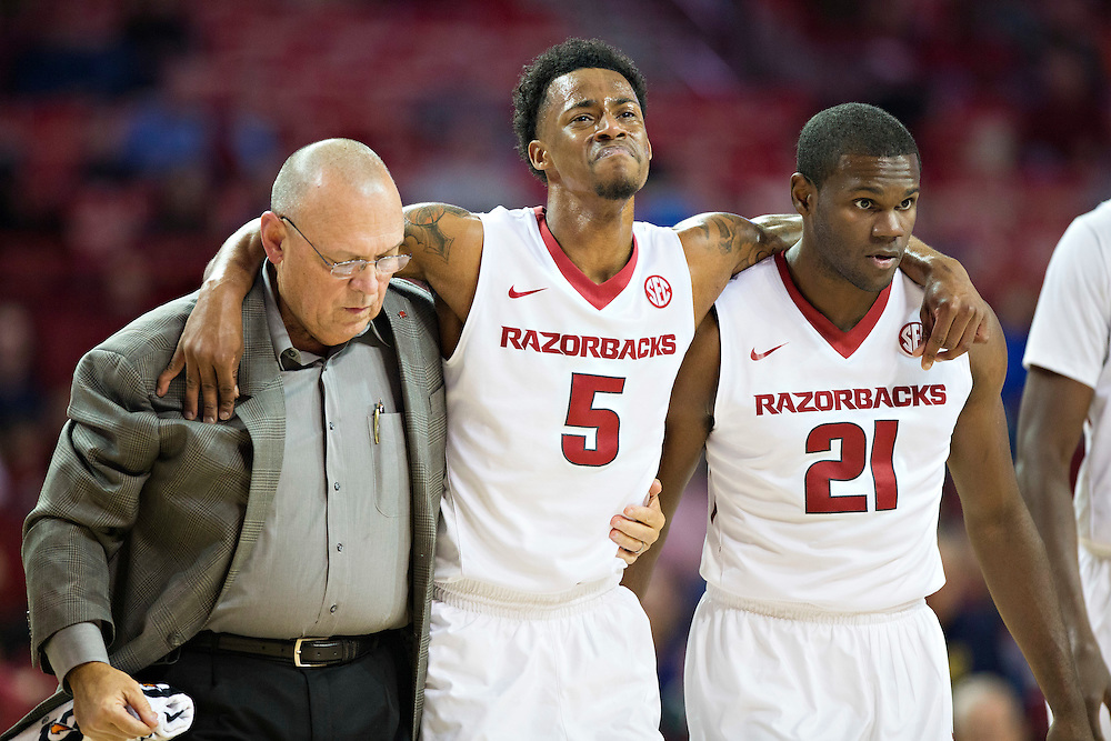 FAYETTEVILLE, AR - NOVEMBER 18:  Trainer Dave England and Manuale Watkings #21 help Anthlon Bell #5 of the Arkansas Razorbacks off the court after he twisted his ankle during a game against the Akron Zips at Bud Walton Arena on November 18, 2015 in Fayetteville, Arkansas.  The Zips defeated the Razorbacks 88-80.  (Photo by Wesley Hitt/Getty Images) *** Local Caption *** Dave England; Anthlon Bell; Manuale Watkins