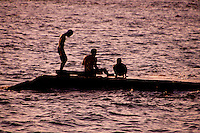 Balinese man and sons on an ocean jetty in Candidasa, Bali, Indonesia