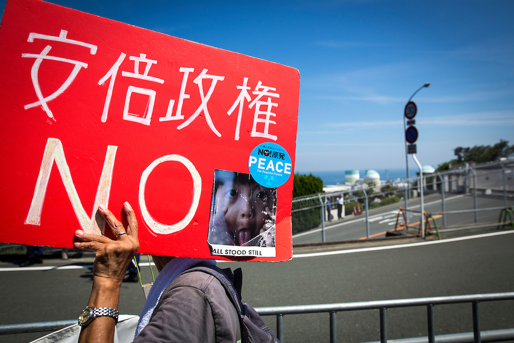 EHIME, JAPAN - AUGUST 11 : Anti-nuclear protester with placard is seen in front of Ikata Nuclear Power Plant to protest against the restarting of a nuclear reactor on August 11, 2016 in Ikata, Ehime prefecture, northwestern Shikoku, Japan. The No. 3 reactor of the nuclear plant is expected to resume operations this week after The Nuclear Regulation Authority (NRA's) has completed it's final inspections of the plant's operational safety measures. The plant has not generated nuclear power since Japan's 2011 nationwide shutdown of all nuclear plants in the aftermath of the Fukushima Daiichi nuclear disaster. Ikata Nuclear Power Plant will be the third nuclear power plant in Japan to become operational. (Photo by Richard Atrero de Guzman/NURPhoto)