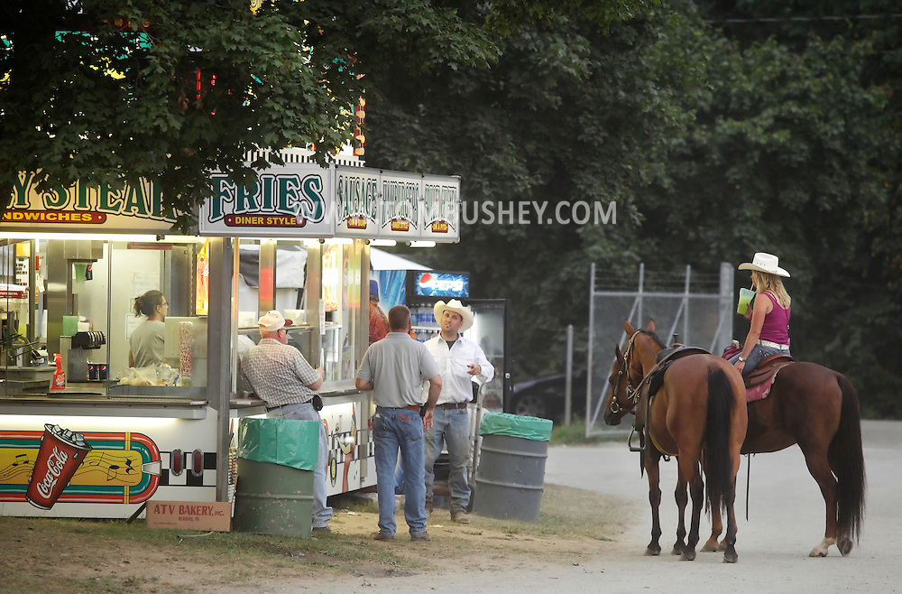 Augusta, New Jersey - Men talk at a refreshment stand while a woman waits on her horse at the New Jersey State Fair and Sussex County Farm and Horse Show on Aug. 11, 2010.