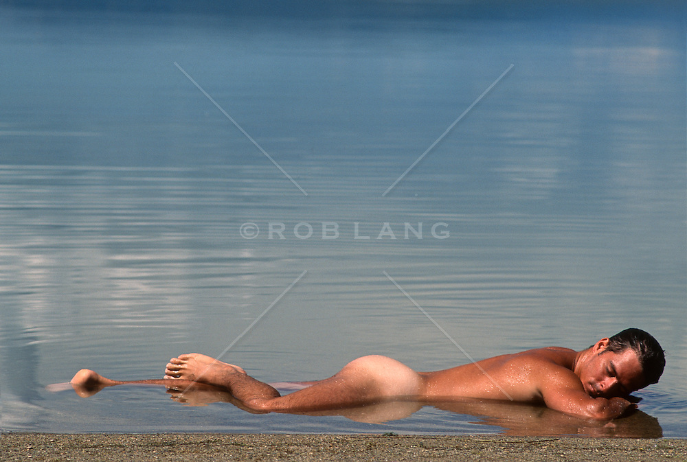 sexy naked man resting in shallow water in a lake