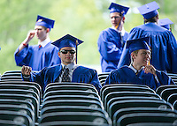 Gilford High School seniors take a few quiet moments prior to the procession for their graduation ceremony Sunday morning in the upper seats at Meadowbrook Pavilion.  (Karen Bobotas/for the Laconia Daily Sun)