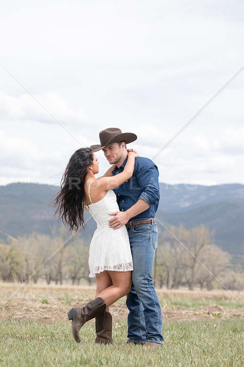 romantic cowboy couple outdoors on a mountain range