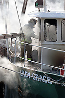 Gloucester: .A Gloucester firefighter works on the fire in the Lady Grace fishing vessel at Rose Marine Tuesday morning. The fire, caused by a spark from a welding torch, gutted much of the interior of the boat. The Lady Grace was used as the Andrea Gail in the film The Perfect Storm..Photo by Mike Dean/Gloucester Daily Times. Monday, March 22, 2004