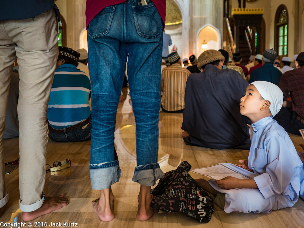 06 JULY 2016 - BANGKOK, THAILAND:  A boy watches men pray in Ton Son Mosque in the Thonburi section of Bangkok before Eid services. Eid al-Fitr is also called Feast of Breaking the Fast, the Sugar Feast, Bayram (Bajram), the Sweet Festival or Hari Raya Puasa and the Lesser Eid. It is an important Muslim religious holiday that marks the end of Ramadan, the Islamic holy month of fasting. Muslims are not allowed to fast on Eid. The holiday celebrates the conclusion of the 29 or 30 days of dawn-to-sunset fasting Muslims do during the month of Ramadan. Islam is the second largest religion in Thailand. Government sources say about 5% of Thais are Muslim, many in the Muslim community say the number is closer to 10%.       PHOTO BY JACK KURTZ