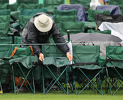 April 7, 2018 - Augusta, GA, USA - A patron tries to keep his chair dry on the 18th hole during the third round of the Masters Tournament on Saturday, April 7, 2018, at Augusta National Golf Club in Augusta, Ga. (Credit Image: © Curtis Compton/TNS via ZUMA Wire)