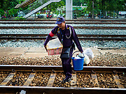 31 MAY 2017 - CHACHOENGSAO, THAILAND:  A train station security guard carries a vendor's supplies to a Bangkok bound train at the train station in Chachoengsao, a provincial town about 50 miles and about an hour by train from Bangkok. The train from Chachoengsao to Bangkok takes a little over an hour but traffic on the roads is so bad that the same drive can take two to three hours. Thousands of Thais live outside of Bangkok and commute into the city for work on trains, busses and boats.      PHOTO BY JACK KURTZ
