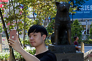 An Asian tourist takes a selfie with a smart phone in front of the Statue of Hachiko dog in Hachiko Square in Shibuya, Tokyo, Japan Friday July 20th 2018