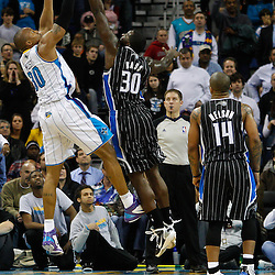 January 12, 2011; New Orleans, LA, USA; New Orleans Hornets power forward David West (30) shoots over Orlando Magic power forward Brandon Bass (30) during the fourth quarter at the New Orleans Arena. The Hornets defeated the Magic 92-89.  Mandatory Credit: Derick E. Hingle