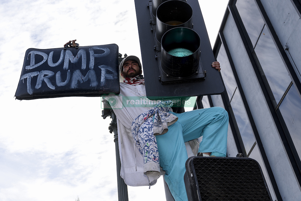 November 12, 2016 - Los Angeles, California, United States - A protester who climbed a traffic light during an anti-Trump protest in Los Angeles, California November 12, 2016. According to the LAPD an estimated crowd of nine thousand people participated, making this the largest anti-Trump protest to date in the city. (Credit Image: © Ronen Tivony/NurPhoto via ZUMA Press)