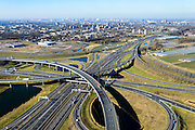 Nederland, Zuid-Holland, Rotterdam, 18-02-2015; Knooppunt Ridderkerk, verkeersknooppunt A15 en A16, bijgenaamd 'Ridderster'. Skyline Rotterdam. Klaverblad met opritten, afritten en fly-overs. De waterpartijen zijn kunstmatige aangelegd en kunnen dienen als bluswater ingeval van calamiteiten.<br /> Ridderkerk junction, junction A15 / A16, nicknamed 'Ridder star'. Cloverleaf type junction, with ramps, exit ramps and flyovers. The ponds are man-made, the water can be used for firefighting in case of emergencies.<br /> luchtfoto (toeslag op standard tarieven);<br /> aerial photo (additional fee required);<br /> copyright foto/photo Siebe Swart