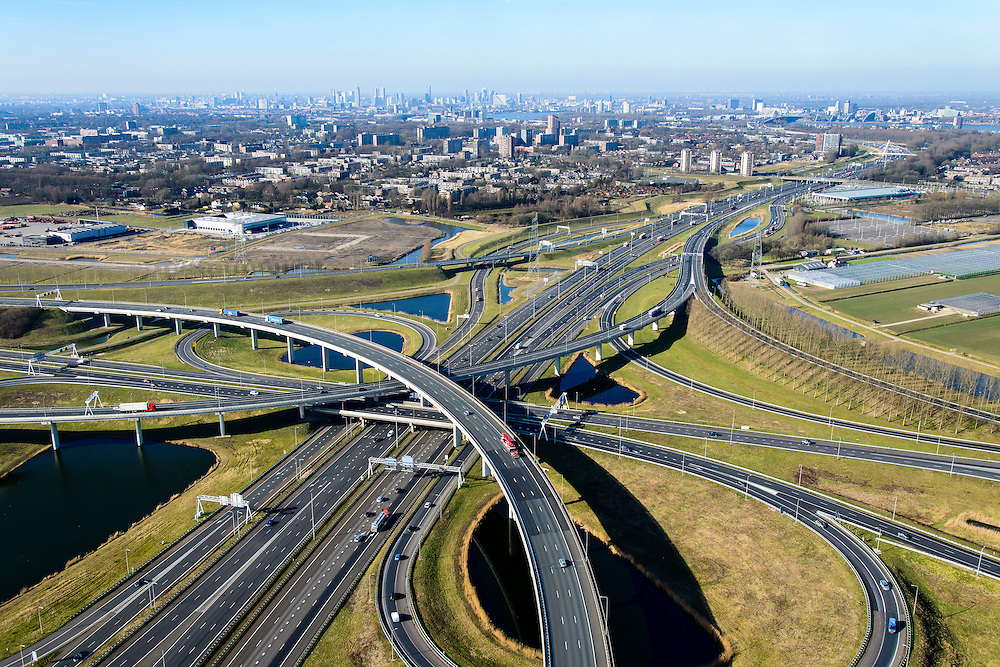 Nederland, Zuid-Holland, Rotterdam, 18-02-2015; Knooppunt Ridderkerk, verkeersknooppunt A15 en A16, bijgenaamd 'Ridderster'. Skyline Rotterdam. Klaverblad met opritten, afritten en fly-overs. De waterpartijen zijn kunstmatige aangelegd en kunnen dienen als bluswater ingeval van calamiteiten.<br /> Ridderkerk junction, junction A15 / A16, nicknamed 'Ridder star'. Cloverleaf type junction, with ramps, exit ramps and flyovers. The ponds are man-made, the water can be used for firefighting in case of emergencies.<br /> luchtfoto (toeslag op standard tarieven);<br /> aerial photo (additional fee required);<br /> copyright foto/photo Siebe Swart
