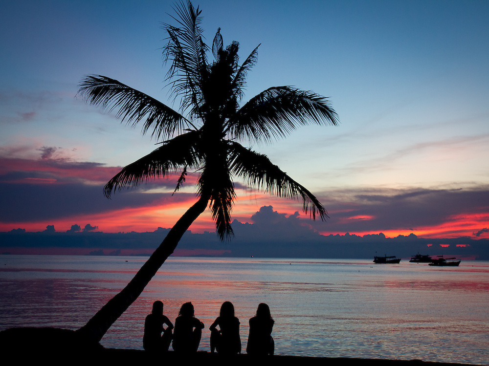 Four friends under a palm tree watch the sun set over the ocean on Koh Tao island, Thailand.