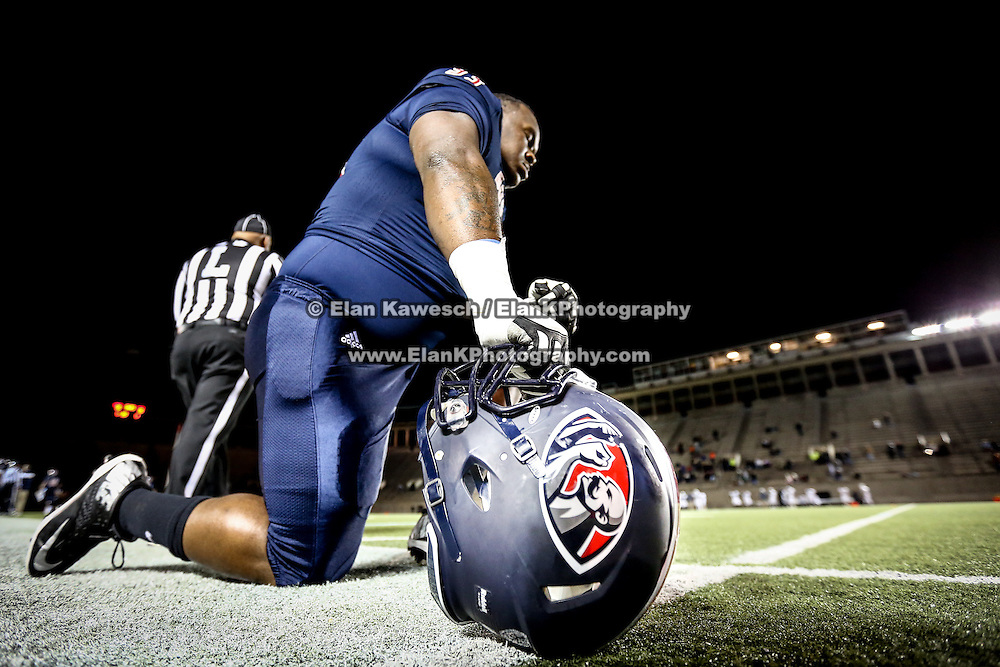 Johnnie Farms #93 of the Boston Brawlers kneels on the sideline with his Brawlers helmet prior to the first ever Boston Brawlers home game at Harvard Stadium on October 24, 2014 in Boston, Massachusetts. (Photo by Elan Kawesch)