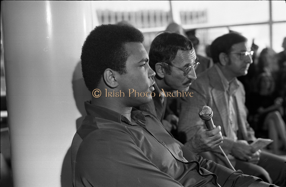 Muhammad Ali In Dublin..1972..11.07.1972..07.11.1972..11th July 1972..Prior to his fight against Al 'Blue' Lewis at Croke Park, Dublin, former World Heavyweight Champion, Muhammad Ali arrives at Dublin Airport. The fight was part of his build up for for a championship fight against the current World Champion, 'Smokin'  Joe Frazier. Ali had been stripped of the title partly due to his refusal to join the American military during the Vietnam War, which he had opposed...Image of Muhammad Ali, boxing promoter Harold Conrad, and trainer Angelo Dundee, as they take questions from the assembled media.