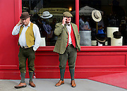 © Licensed to London News Pictures. 14/09/2012. Goodwood, UK Two men talk on their mobile phones outside a hat shop. People enjoy the atmosphere at the 2012 Goodwood Revival Meeting today 14 September 2012. The event recreates the glorious days of motor racing and participants are encouraged to dress in period dress. Photo credit : Stephen Simpson/LNP