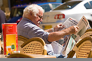 Man reading a newspaper outside a french cafe